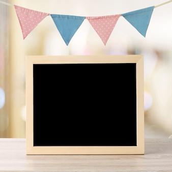 カラフルな黒板は、カラフルなパーティーフラグの上に立って、テキストのコピースペースと背景をぼかし