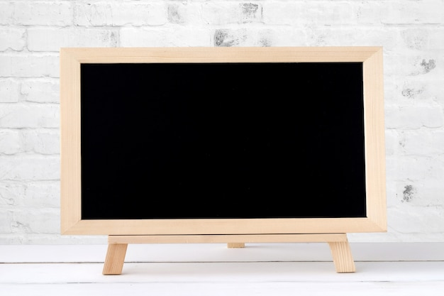Blank chalkboard standing on white table over white brick wall background