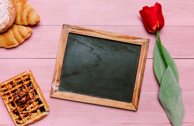 Blank chalkboard with belgian waffle and tulip