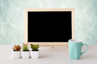Blank chalkboard with coffee mug and smaill tree pots