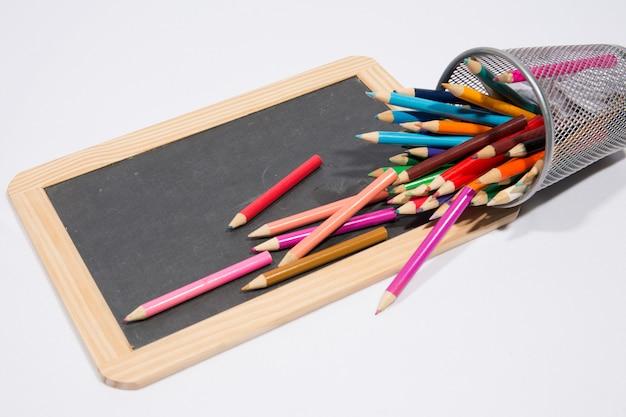 色とりどりの鉛筆クレヨンで空白の黒板-メッセージ用のコピースペース