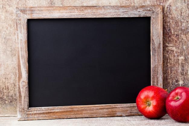 Пустая доска с красными яблоками над деревянным столом.