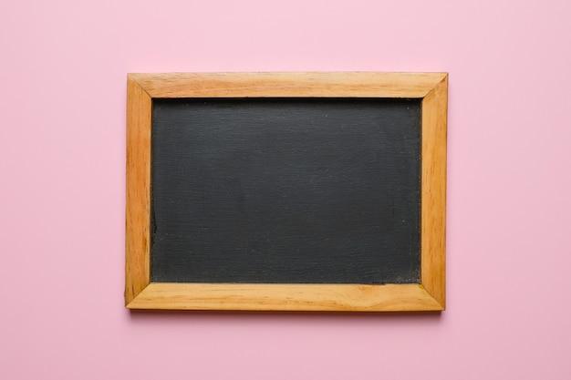 ピンクの背景に分離された木製フレームと空白の黒板。スペースに独自のテキストを追加できます。