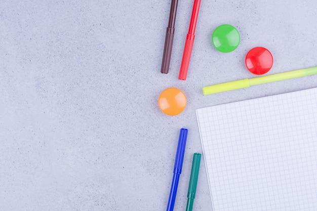 Un documento controllato in bianco con perni e matite multicolori intorno