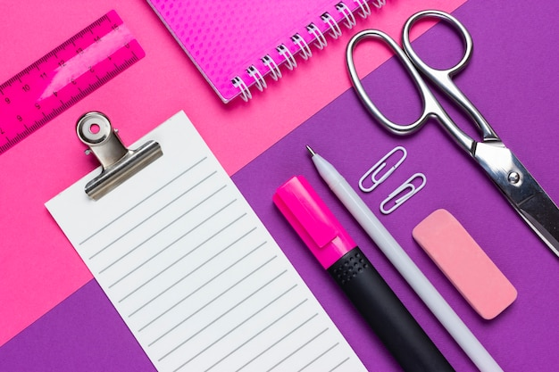 Blank checklist scissors, copybook, pen, eraser, paper clip and marker on pink and purple background. top view