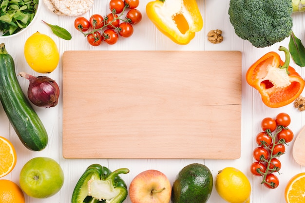 Blank chopping board surrounded with colorful vegetables and fruits on white table