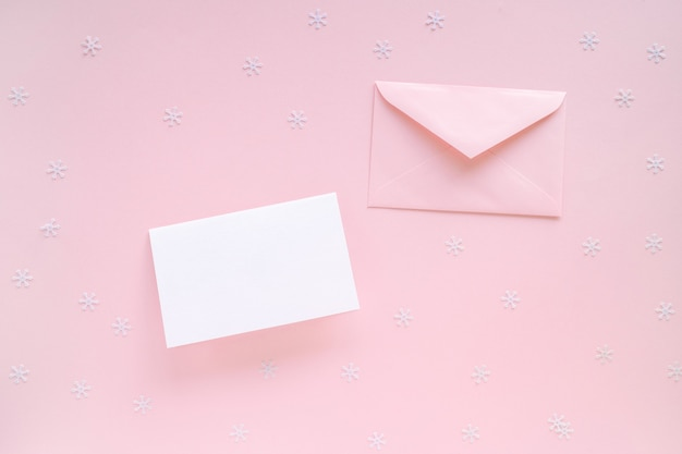 Blank christmas card and pink envelope with christmas decorations on pink surface
