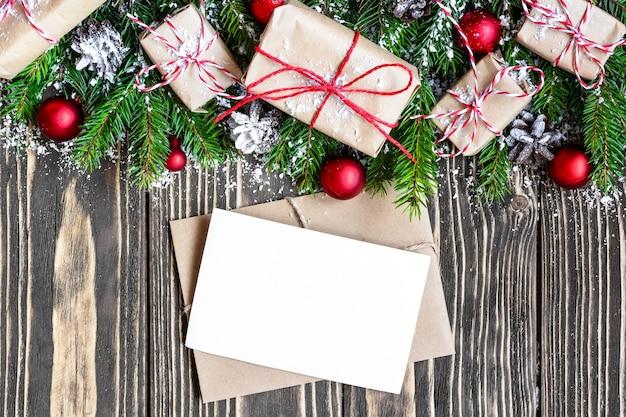 Пустая рождественская открытка и конверт с еловыми ветками, подарочными коробками, украшениями и сосновыми шишками