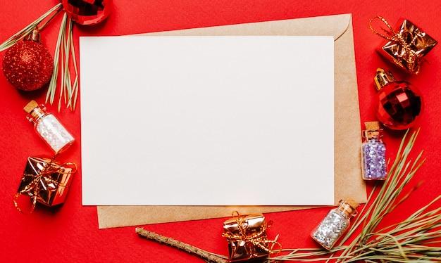 Пустая рождественская записка с подарком, еловой веткой и игрушкой на красном