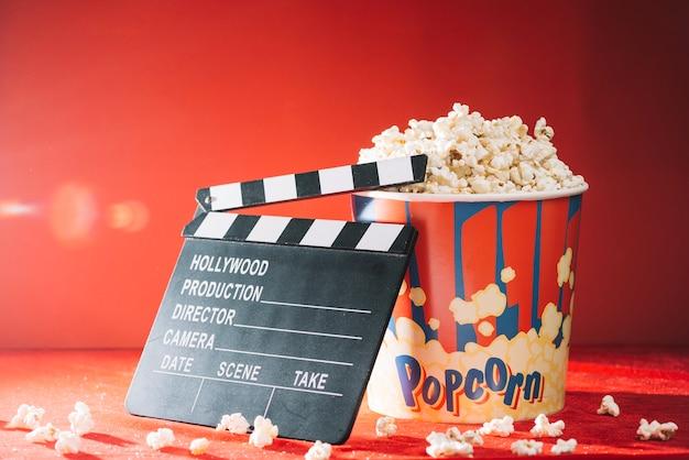 Blank clapperboard near big popcorn bucket