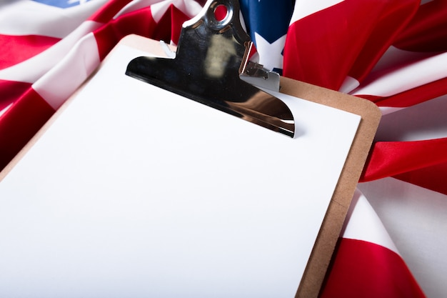 Blank clip board and usa flag on wooden background