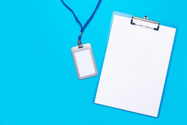 밝은 파란색 표면에 파란색 졸라 매는 끈이있는 빈 클립 보드 및 플라스틱 이름 배지