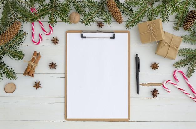 空のクリップボード、白い木製の背景にクリスマスの装飾。フラットレイ、トップビューモックアップ、