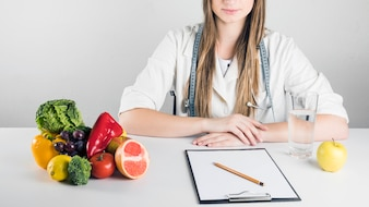 Blank clipboard; healthy food and glass of water on desk