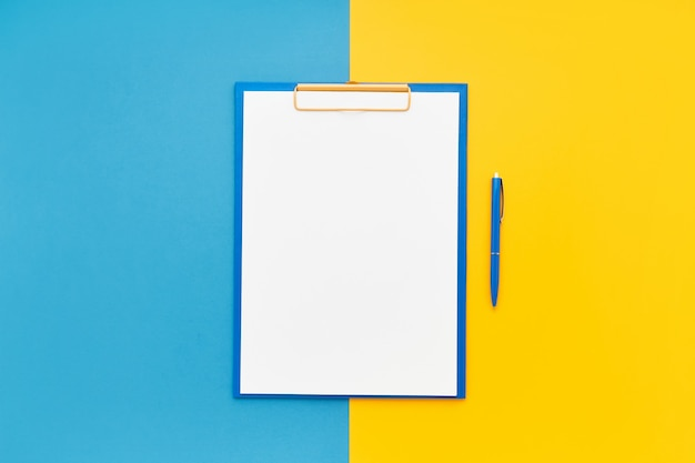 Blank clipboard mockup and blue ballpoint pen on blue-yellow color background