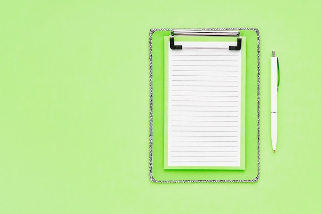 Blank clipboard mockup and white ballpoint pen on green color background