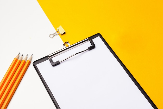 Blank clipboard paper on bright yellow