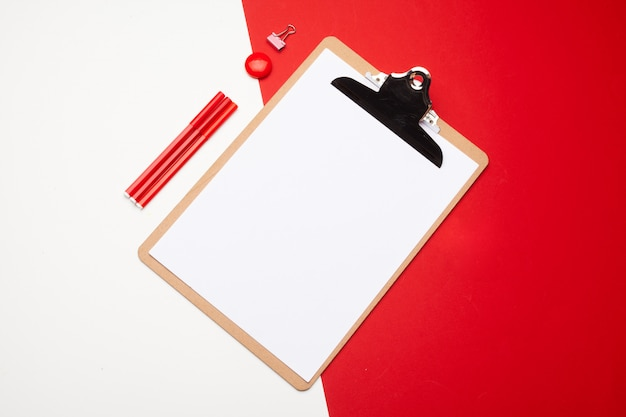 Blank clipboard paper on red and white paper background