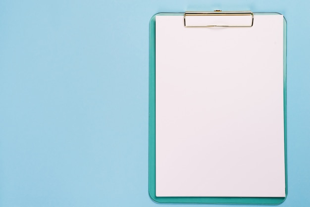 Blank clipboard on pastel blue color background with copy space, flat lay