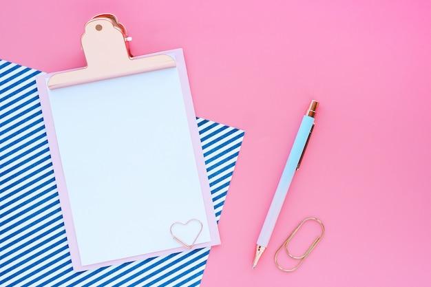 空のクリップボード、ペン、ペーパークリップ、ピンクのテーブルに青い縞模様の紙。フラットなレイアウト、トップビュー。