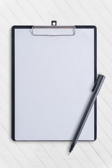 Blank clipboard and pen on white concrete table
