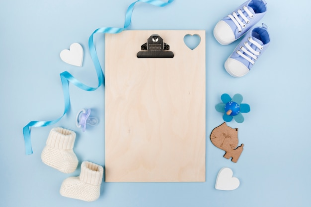 Blank clipboard with baby shoes