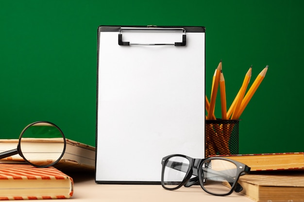 Blank clipboard with copy space and school supplies front view