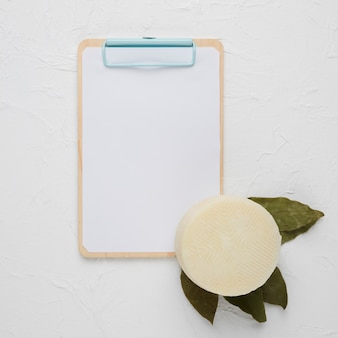 Blank clipboard with spanish manchego cheese and dried bay leaves on white concrete background