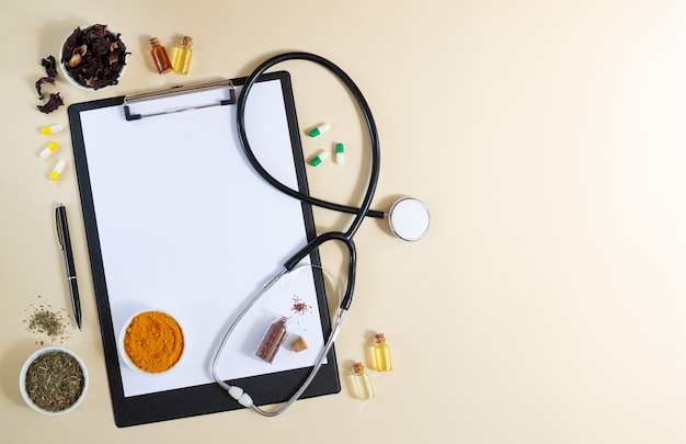 Blank clipboard with stethoscope, various healthy herbs, spices, capsules and oils top view