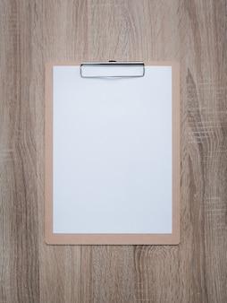 Blank clipboard on wooden desk.
