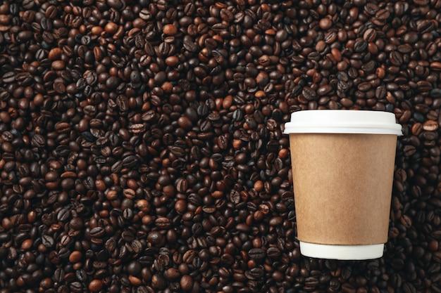 Пустая кофейная чашка на предпосылке кофейных зерен, космосе для текста