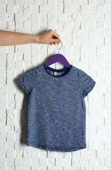가벼운 질감의 벽에 빈 색 티셔츠