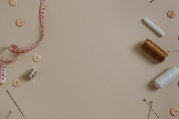 ソーイングツール付きの空白のコピースペース:ボタン、スプール、指ぬき、巻尺、ニュートラルベージュの針