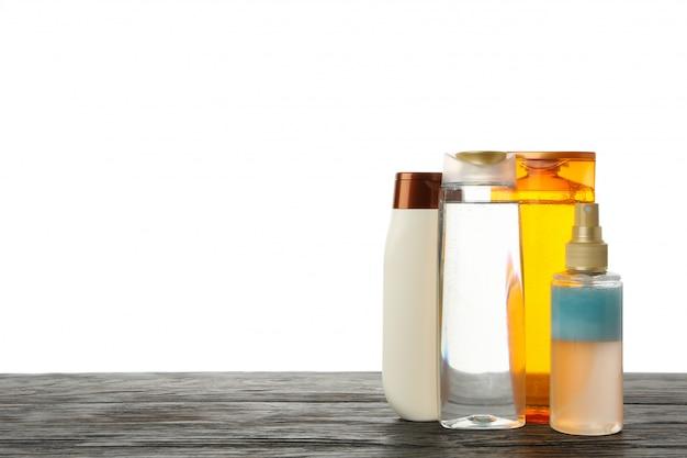 Пустые бутылки косметики на деревянном столе, изолированные на белом фоне
