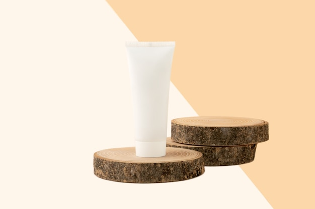 Blank cosmetics tube stand on the top of wooden cut.two slices behind like podium for product.beautiful pastel beige isometric background.organic copcept.