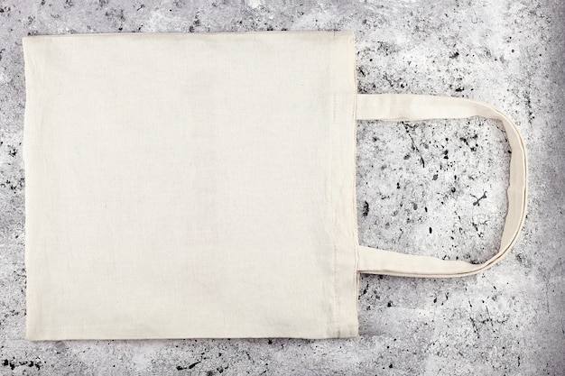 Blank cotton tote bag, design mockup. handmade shopping bag on concrete table