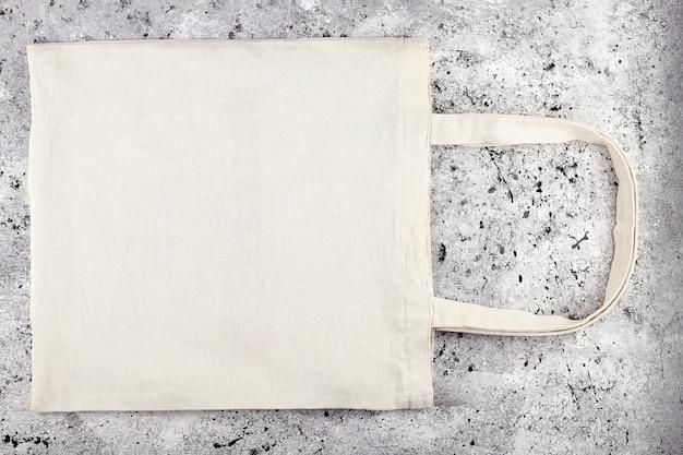 빈 코튼 토트 백, 디자인 모형. 콘크리트 테이블에 수제 쇼핑백