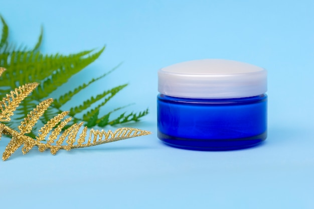 Blank cream jar with golden fern palm leaves. cosmetic skincare products, modern concept of organic beauty trend.