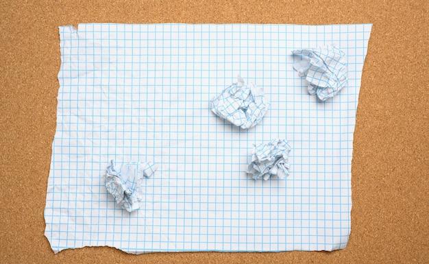 Чистый мятый белый лист бумаги в клетке и мятые шары, вид сверху