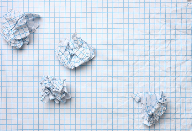 Blank crumpled white sheet of paper in a cage and crumpled balls, top view