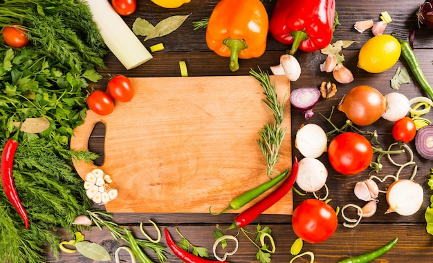 Blank cutting board surrounded by peppers, herbs, tomatoes, mushrooms and other savory flavored vegetables