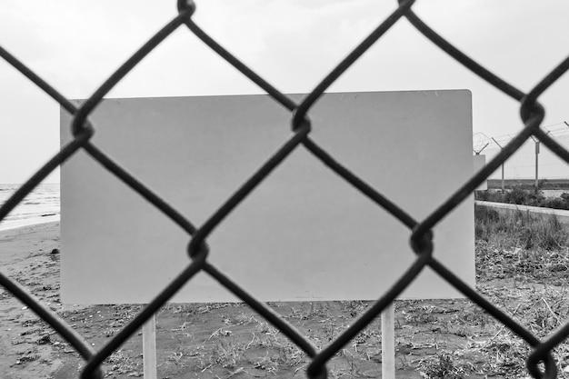 철망 울타리를 통해 빈 위험 또는 경고 표시 - 자신의 텍스트를 위한 공간. 흑백 이미지