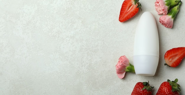 Blank deodorant, strawberry and flowers on white textured table