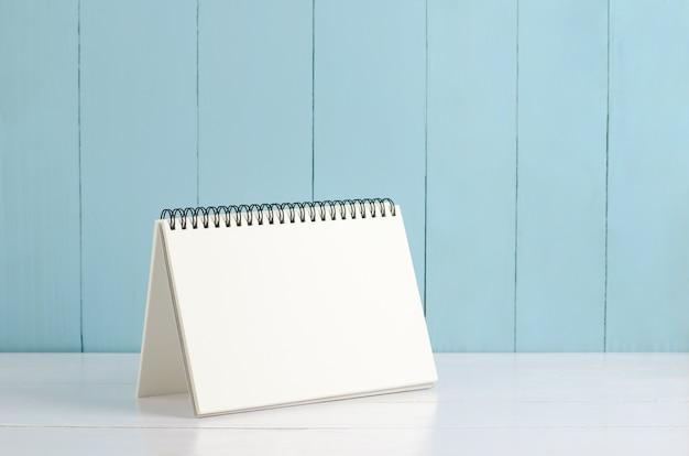 Blank desk calendar on white and blue wooden background