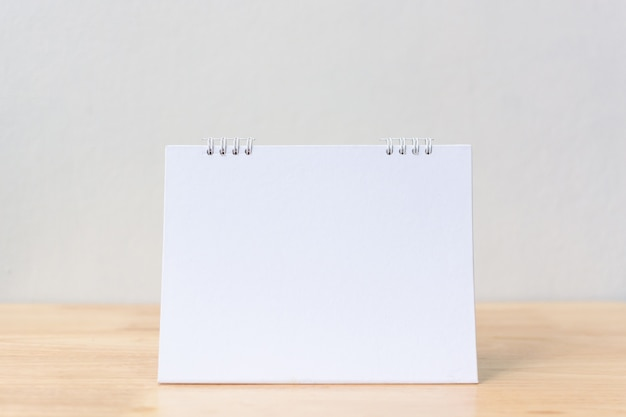 Blank desk calendar on wood table.