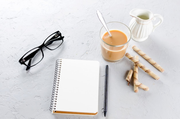 Blank diary, pen, cup of coffee and glasses on grey background