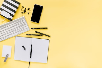 Blank diary with pens; bulldog paper clips; keyboard and cellphone on yellow background