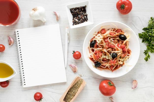 Blank diary and yummy spaghetti pasta with fresh ingredient on white wooden table