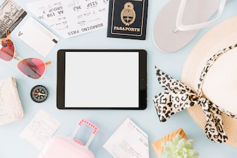 Blank digital tablet surrounded with boarding passes; visiting card; sunglasses; compass; cactus plant; hat; passport; miniature travel bag and flip flops