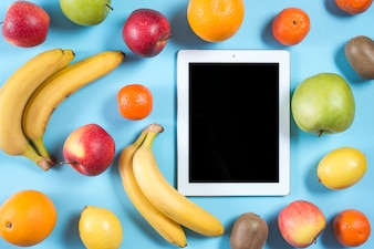 Blank digital tablet surrounded with whole healthy fruits on blue background